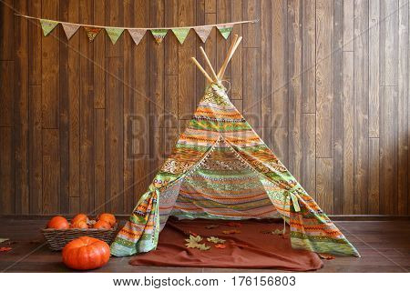 A colored fabric tent with a plaid and pumpkins in front of a wooden wall in the room