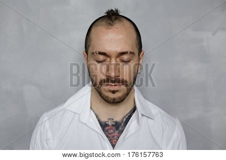 Close up portrait of bearded tottooed man in white shirt with closed eyes. Relaxing and meditation concept. Dj thinking about new music and planning his action