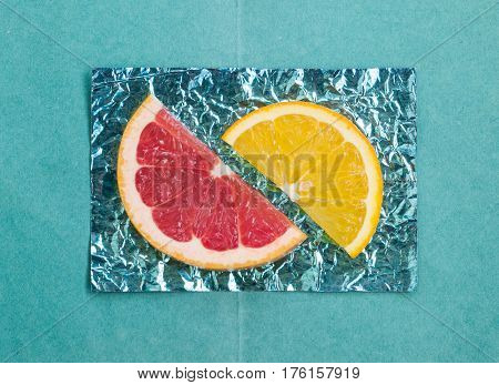 Orange and slices and grapefruit on stands made of colored foil
