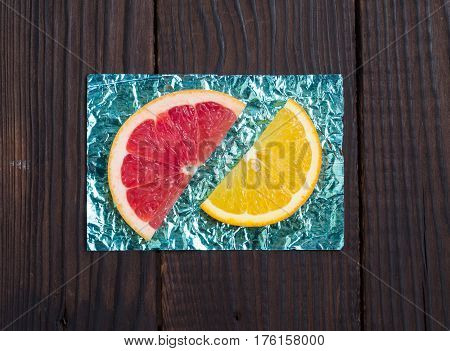 Orange and slice and grapefruit on stands made of colored foil on a wooden surface