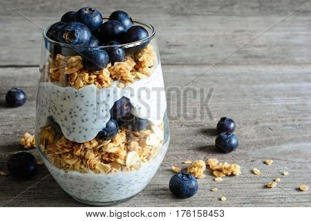 Yogurt with granola fresh blueberries chia seeds and oats in a glass over old wood background. close up