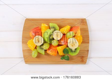 pile of fresh fruit salad on wooden cutting board
