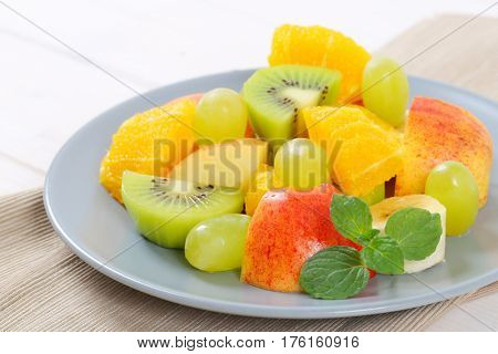 plate of fresh fruit salad on beige place mat