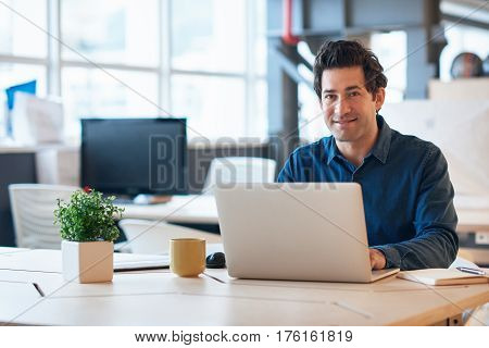 Portrait of a smiling young businessman wearing casual clothes sitting at a desk in a modern office working on a laptop