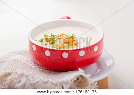 A bowl of creamy cauliflower soup with shrimps