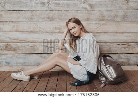Fashion lifestyle portrait of young pretty woman sitting in wooden room. Processed with VSCO f3 preset