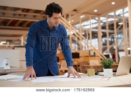 Casually dressed focused young businessman leaning over a desk in a modern office using a laptop and sorting through paperwork