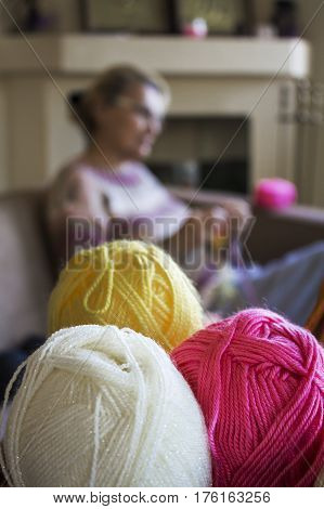 Multicolored thread in tangles and Old women on the background looking at her hands holding knitting needles and a yellow thread in her hands to tie a scarf from them