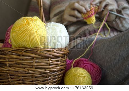 knitting needles and a colorful thread and women on the background