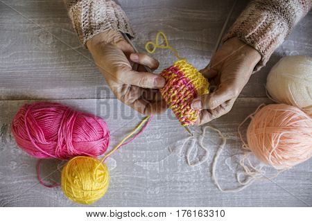Women's  Hands Hold Knitting Needles And A Colorful Thread To Tie A Scarf From Them