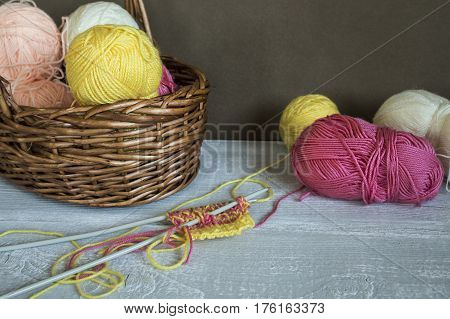 Knitting Needles And A Colorful Thread On The Table
