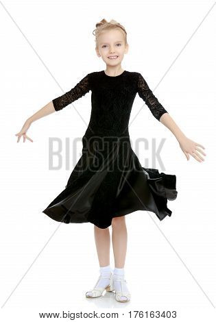The slender little blonde girl dancer in the long dress of black color made specifically for performing .The girl gracefully spinning , the edges of her dress fluttering in the wind.Isolated.