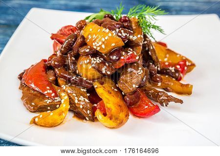 delicious braised beef with red beans and peppers on white plate