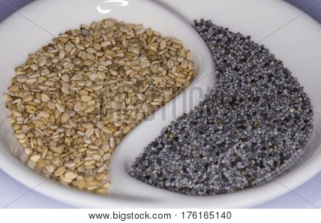 Sesame and poppy seeds in yin yang cup