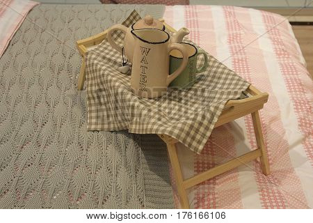 Wooden tray with coffee and interior decor on the bed with linen