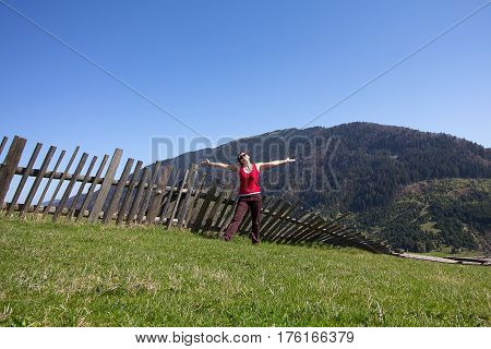 Woman is a tourist on the background of a fence in the countryside. Journey