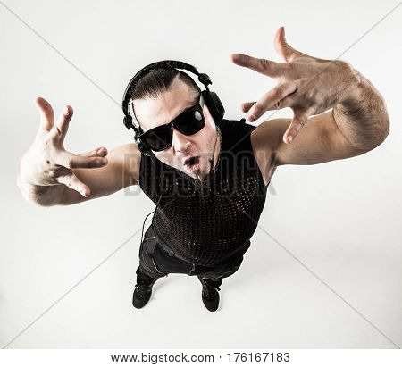 view from the top - DJ - rapper with headphones on a light background performs a rap song.the photo has a empty space for your text