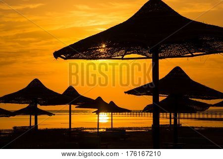 Sunset at the sea with silhouette of beach umbrellas in Egypt, Red sea
