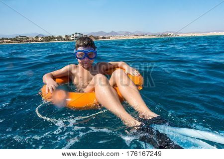 Smiling boy in swimming mask floating on lifebuoy in the sea