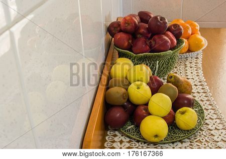 Tavern of fruits with orange apples and kiwis reflected in wall