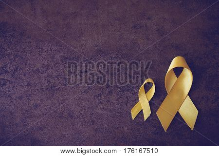 yellow gold ribbons on hands Sarcoma Awareness Bone cancer Liver cancer Bladder Cancer childhood cancer awareness