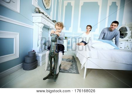 girl riding on wooden horse in the bedroom of the parents