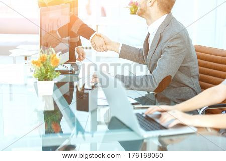 handshake of business partners on the background of the desktop .the photo has a empty space for your text.