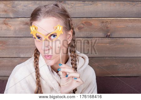 Young woman with yellow glasses on a stick