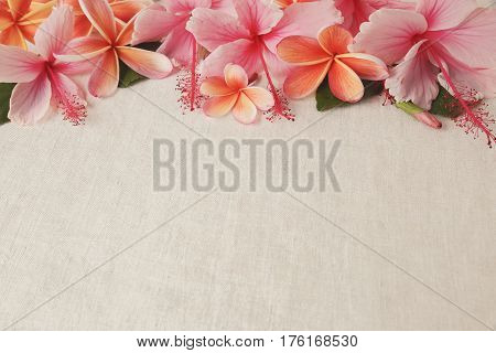 Frangipani Plumeria Hibiscus flowers on linen copy space background selective focus vintage tone