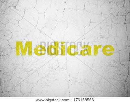 Medicine concept: Yellow Medicare on textured concrete wall background