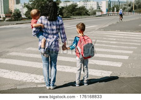 Mother and her children waiting at zebra crossing on their morning way to school