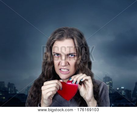 Female with angry face holding red heart on stick
