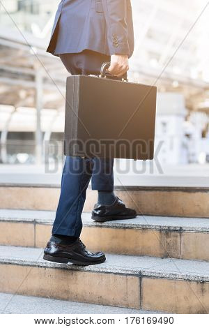 Close up shot of businessman holding leather briefcase while walking upward on the stair outdoor in city.
