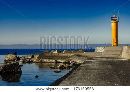 Yellow Lighthouse On Breakwater Dam