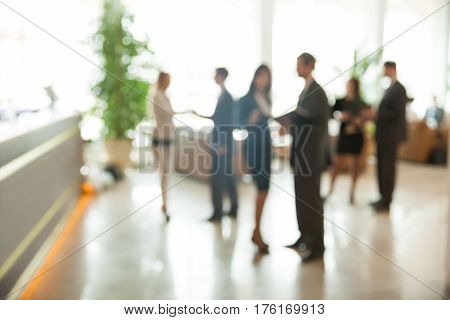 Blurred background : employees work in the lobby, spacious office. photo has a empty space for your text