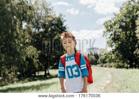 Portrait of a sad schoolboy on his morning way to school