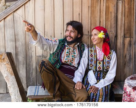 Young happy couple sitting in traditional Bulgarian costume