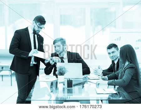 photo in retro style - business partners discuss the profits before signing a new contract at the workplace in a modern office.the photo has a empty space for your text