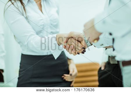 closeup of handshake of business partners on the background of the office