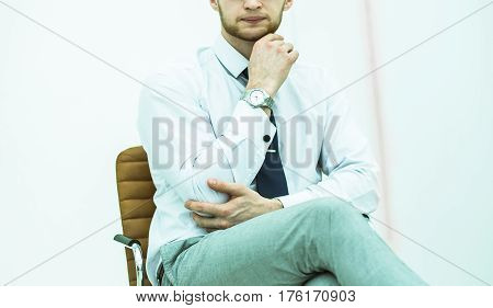 portrait of a businessman sitting on a chair in the spacious office.the photo has a empty space for your text