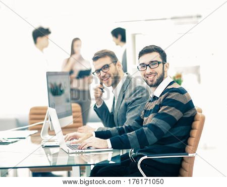 business team discussing marketing schemes in the workplace on the background of the company's employees.the photo has a empty space for your text.