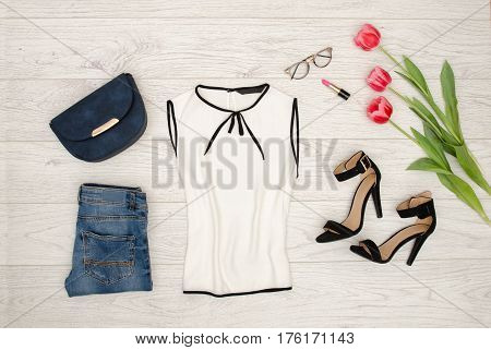 Fashion concept. White blouse blue handbag glasses lipstick black shoes and pink tulips. Top view light wood background