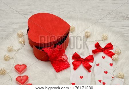 Fashionable concept. Red box with lace underwear heart-shaped candles white stockings with a bow and garland on white fur. Close-up
