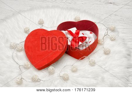 Open red box with heart shaped red and white linen white fur. Top view