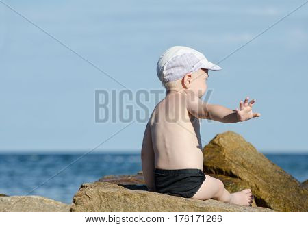Gesture not to bother. Little boy in swimming trunks sits on the seashore place for text