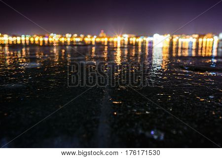 Frozen lake on the background of night city
