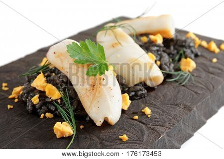 Black squid ink rice and fried calamar on wooden serving board, close-up