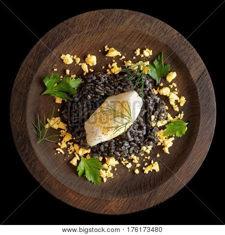 Black squid ink rice and fried calamar on wound wooden plate isolated over black background