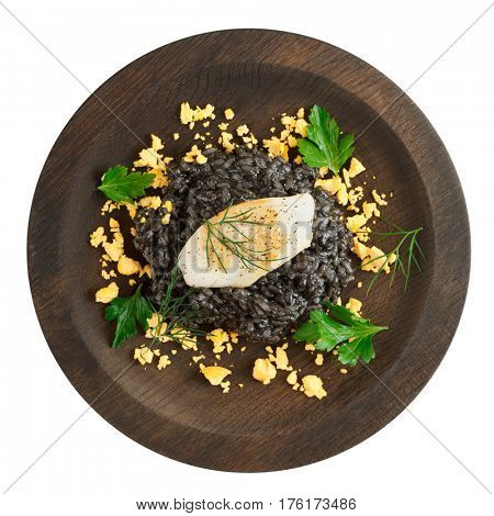 Risotto dyed with squid ink and seared calamar on round wooden plate, isolated on white