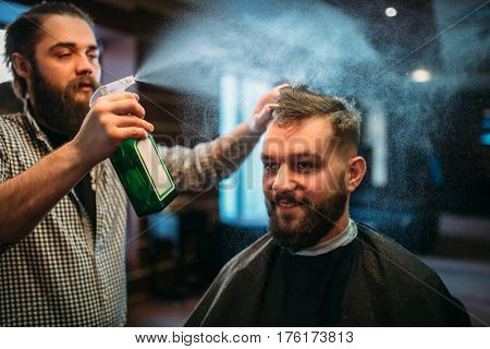 Hairdresser water with spray hair of client man